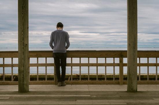 Mężczyzna stoi na drewnianym moście i spogląda w dal
