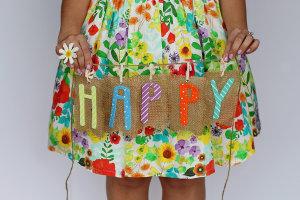 Dziewczyna w sukience trzyma plakietkę z napisem happy