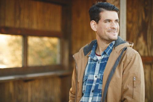 Mężczyzna w kurtce opiera się o drewniany strop i się uśmiecha