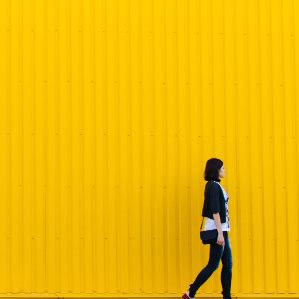 kobieta stoi przy żółtej ścianie