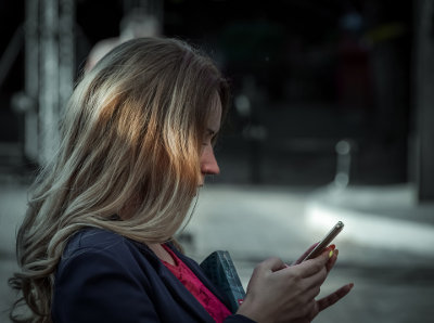 Kobieta wpatruje się w telefon komórkowy