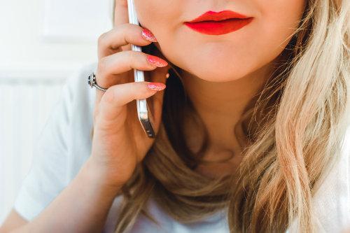 Kobieta z czerwonymi paznokciami rozmawia przez telefon